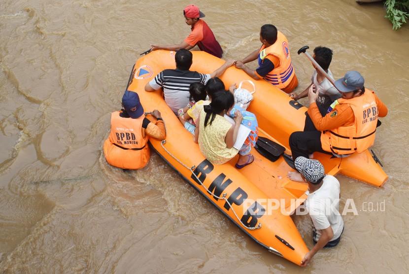 Banjir Madiun. Relawan Badan Penanggulangan Bencana Daerah (BPBD) mengevakuasi warga saat terjadi banjir di Desa Kedungrejo, Pilangkenceng, Kabupaten Madiun, Jawa Timur, Rabu (6/3/2019).