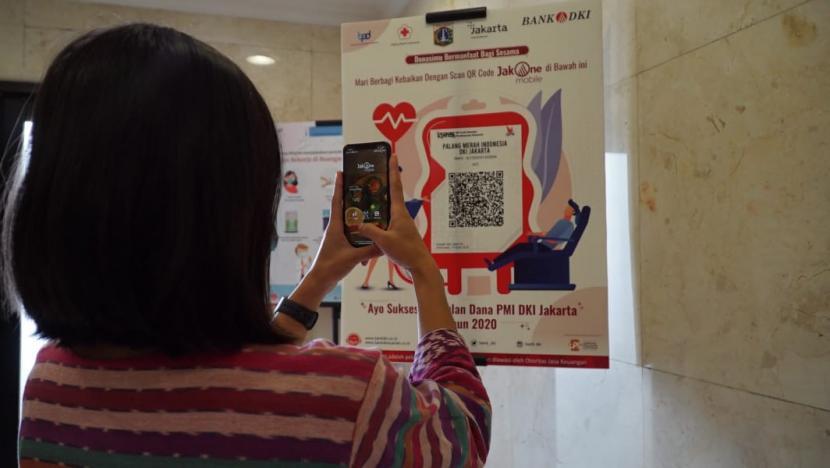 Seorang nasabah menggunakan aplikasi JakOne Mobile dari Bank DKI untuk donasi kemanusiaan.