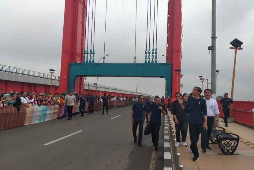 BATIK -- Batik sepanjang 250 meter dibentangkan di sepanjang Jembatan Ampera Palembang untuk menyambut Presiden Jokowi, Sabtu (9/3).
