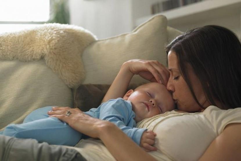 bayi tidur dalam dekapan ibunya