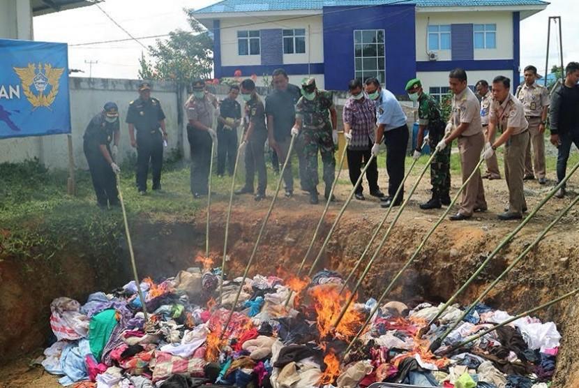 Bea Cukai Entikong memusnahkan pakaian impor ilegal.