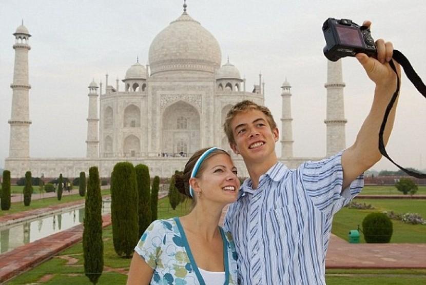 Beberapa turis menjadikan Taj Mahal sebagai spot foto yang menarik