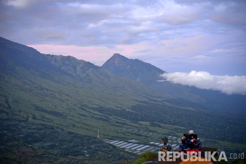 Beberapa wisatawan menikmati matahari terbit Gunung Rinjani dari Bukit Pergasingan, Sembalun, Lombok.   (Republika/ Wihdan Hidayat)