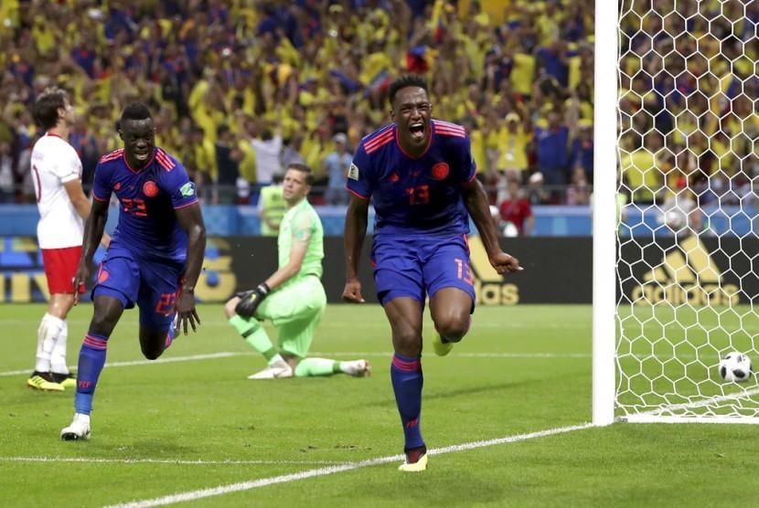 Bek Kolombia, Yerry Mina (kanan) merayakan gol ke gawang Polandia pada laga penyisihan Piala Dunia 2018 di Kazan, Senin (25/6) dini hari WIB.