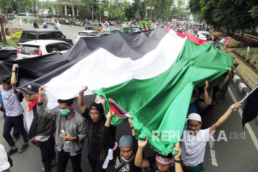 Bendera Palestina berukuran raksasa dibawa serta dalam aksi solidaritas bela Palestina yang diikuti ribuan peserta yang tergabung dalam Aliansi Masyarakat Selamatkan Al Aqsa (AMSA), di depan Gedung Sate, Kota Bandung, Jumat (15/12).