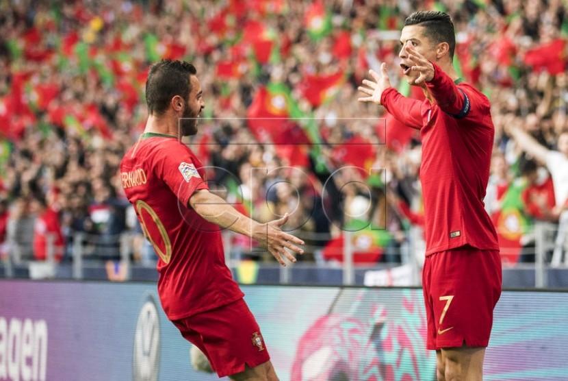Bernardo Silva (kiri) dan Cristiano Ronaldo merayakan kemenangan timnas Portugal.