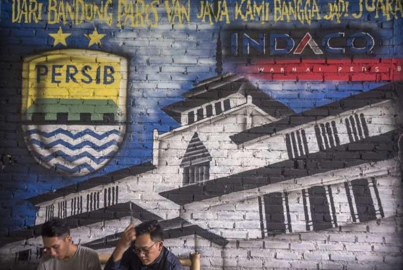 Bobotoh alias pendukung Persib berbincang di depan mural Persib di Bandung, Jawa Barat, Selasa (2/10).