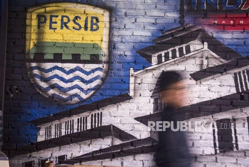 Bobotoh alias pendukung Persib berjalan di depan mural Persib di Bandung, Jawa Barat, Selasa (2/10).