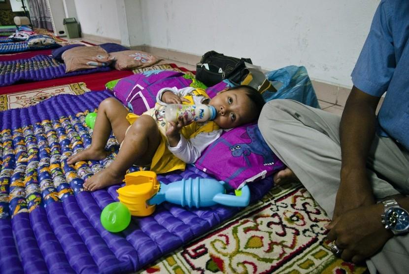 Bocah berusia dua tahun bernama Aulia ditemani ayahnya di Posko Evakuasi Korban Asap di Kantor Wali Kota Pekanbaru, Riau, Rabu (30/9).