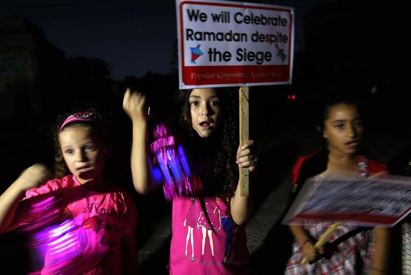 Bocah Palestina membawa lentera Ramadhan sambil melakukan aksi protes pengepungan oleh Israel di Jalur Gaza, Palestina.