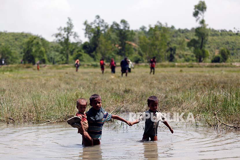 Bocah pengungsi Rohingya melintasi rawa dalam upayanya mengungsi ke wilayah Bangladesh.