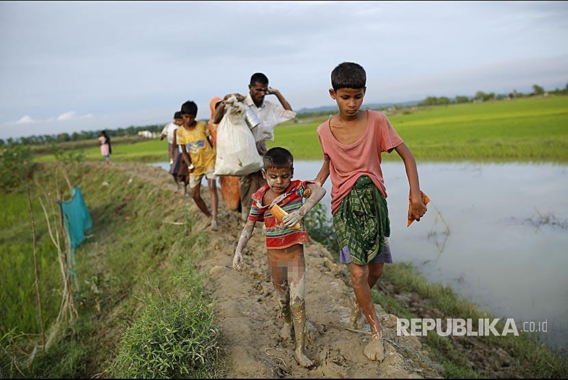 Bocah Rohingya menyusuri jalan berlumpur menuju pengungsian dengan pakaian seadanya di Teknaf, Bangladesh