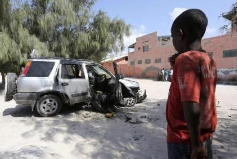 Bocah Somalia memerhatikan rongsokan mobil yang hancur akibat ledakan bom di Ibu Kota Mogadishu.