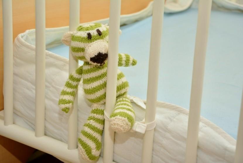 Boneka di tempat tidur bayi.