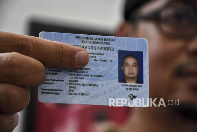 Bonie Nugraha Permana (46) menunjukkan Kartu Tanda Penduduk Elektronik atau e-KTP dengan kolom penghayat kepercayaan, di rumahnya, Kecamatan Panyileukan, Kota Bandung, Jumat (22/2).