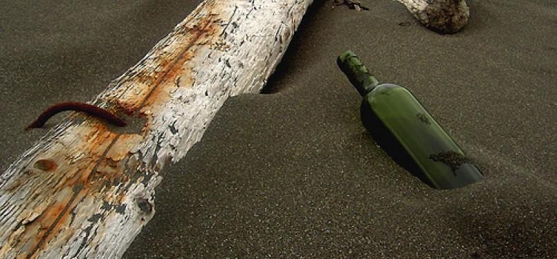 Botol di atas pasir pinggir pantai (ilustrasi).
