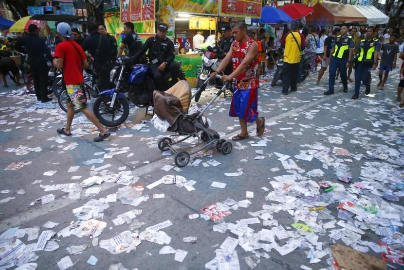 Brosur kampanye berserakan di luar sebuah tempat pemungutan suara pemilu paruh waktu di Manila, Filipina, Senin (13/5).