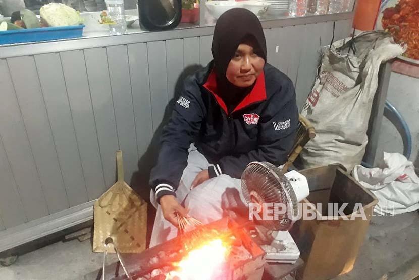 Bu Ari, Penjual Warung Makan Mbah Mo sedang membakar sate landak