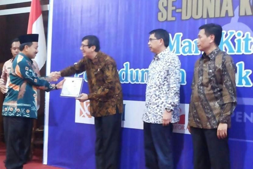Bupati Banjar Sultan H Khairul Saleh (kiri) menerima penghargaan dari Menteri Hukum dan Hak Asasi Manusia Yasonna Laoly karena dinilai peduli terhadap Hak Asasi Manusia (HAM) di Jakarta, Rabu (10/12).