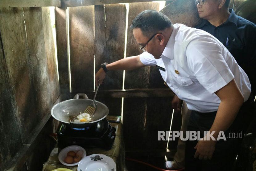 Bupati Musi Banyuasin (Muba) Dodi Reza Alex mencoba memanfaatkan jaringan gas rumah tangga dengan mengoreng telur ayam di rumah warga, Rabu (27/9).