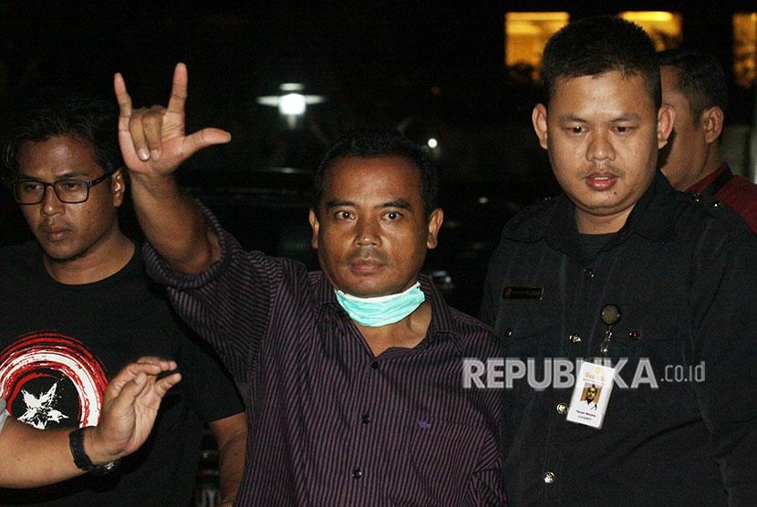 Bupati Purbalingga Tasdi (tengah) mengacungkan salam saat tiba di gedung KPK dengan pengawalan tim penyidik KPK di Gedung KPK, Jakarta, Selasa (5/6).