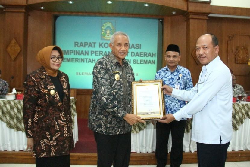 Bupati Sleman, Sri Purnomo, didampingi Wakil Bupati Sleman, Sri Muslimatun, menyerahkan penghargaan HKI Award 2018 di Setda Kabupaten Sleman.