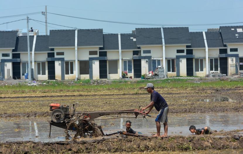 Buruh tani membajak sawah menggunakan traktor dengan latar belakang perumahan di areal persawahan Desa Segodorejo, Kecamatan Sumobito, Jombang, Jawa Timur.