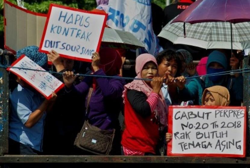 Buruh yang tergabung dalam Konfederasi Serikat Pekerja Nasional (KSPN) berada di atas bak truk sambil membawa poster, saat berunjuk rasa memperingati Hari Buruh Internasional, di Semarang, Jawa Tengah, Selasa (1/5).
