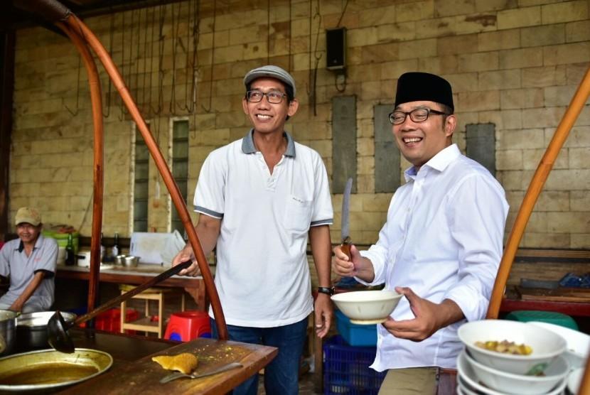Cagub Jabar nomor urut 1 HM Ridwan Kamil (berpeci) mendatangi rumah makan empal gentong H Apud di Cirebon, Selasa (6/3).