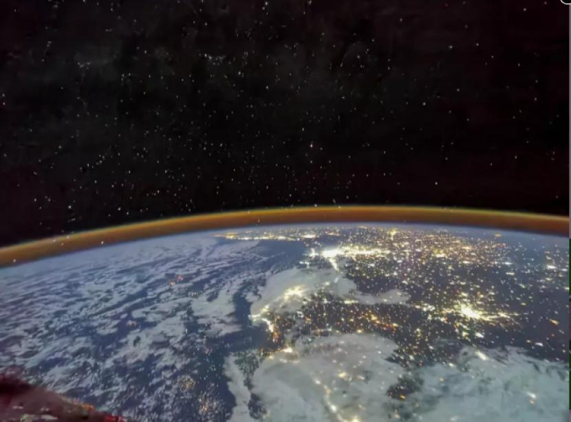 Cahaya berkilauan dalam pemandangan luas Bumi, ruang angkasa, dan bintang-bintang yang diambil dari modul Tianhe dari stasiun ruang angkasa China.