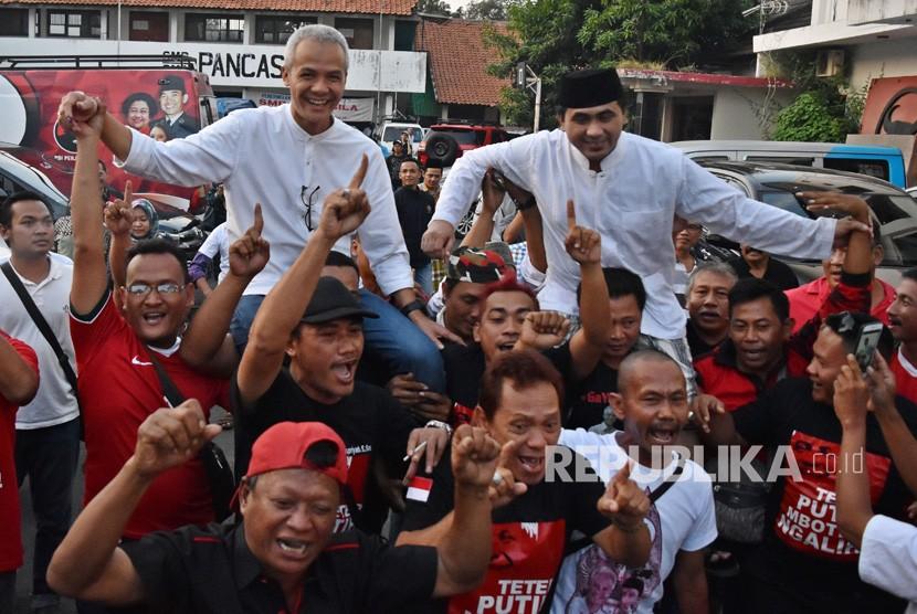 Calon gubernur dan calon wakil gubernur Jawa Tengah Ganjar Pranowo (kiri) dan Taj Yasin dipanggul para pendukung merayakan keunggulan dalam hitung cepat Pilkada Jateng 2018 versi sejumlah lembaga survei di Kantor DPD PDI Perjuangan Jateng, Semarang, Jawa Tengah, Rabu (27/6).