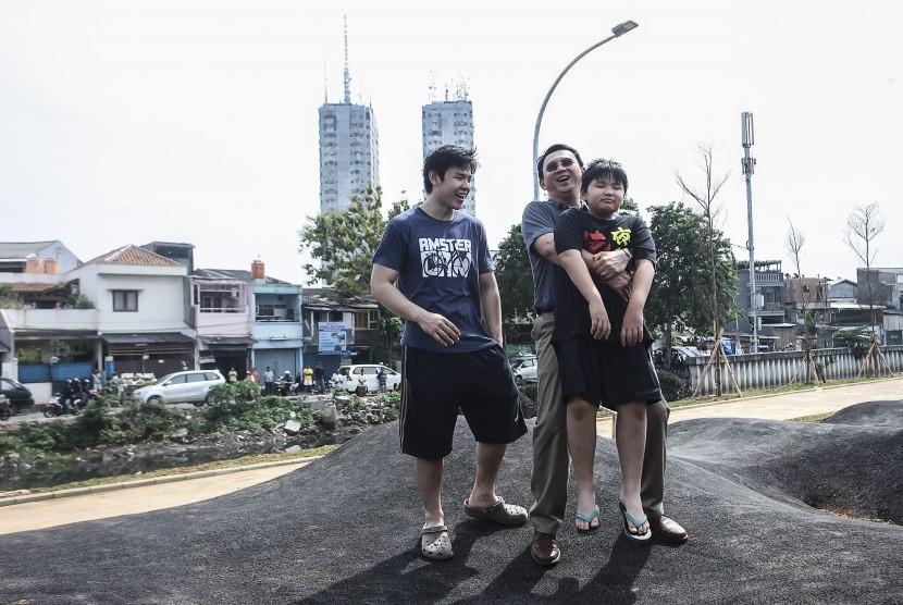 Basuki Tjahaja Purnama atau Ahok bermain bersama kedua anaknya Nicholas Sean Purnama (kiri) dan Daud Albeenner Purnama di Ruang Terbuka Hijau dan Ruang Publik Terpadu Ramah Anak (RTH RPTRA) Kalijodo, Jakarta.