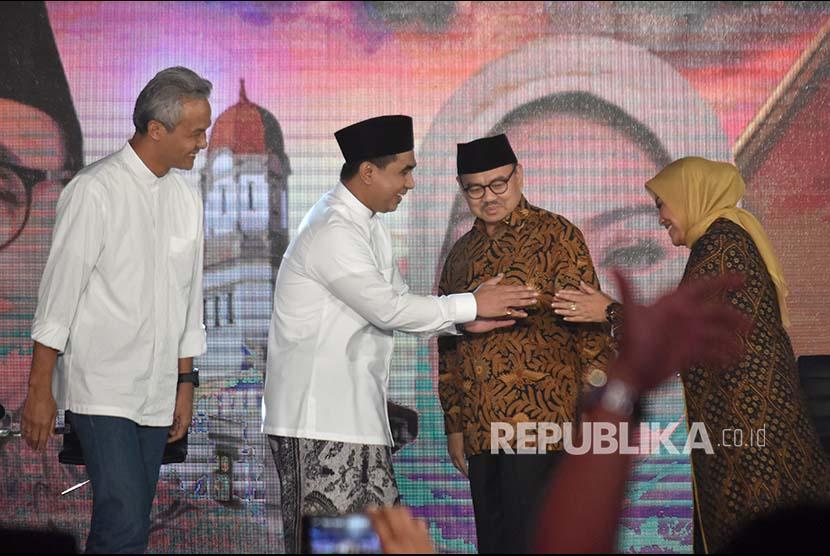 Calon gubernur Ganjar Pranowo (kiri) dan Sudirman Said (kedua kanan) menyaksikan calon wakil gubernur Taj Yasin (kedua kiri) dan Ida Fauzia (kanan) berjabat tangan.