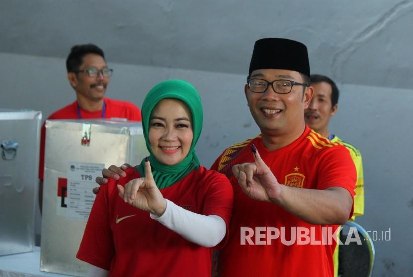 Calon Gubernur Jawa Barat Ridwan Kamil bersama istri Atalia Praratya menunjukan tinta di jari kelingking usai mencoblos dalam Pilkada Serentak 2018, di Tempat Pemungutan Suara (TPS) 21, Cigadung, Kota Bandung, Rabu (27/6).