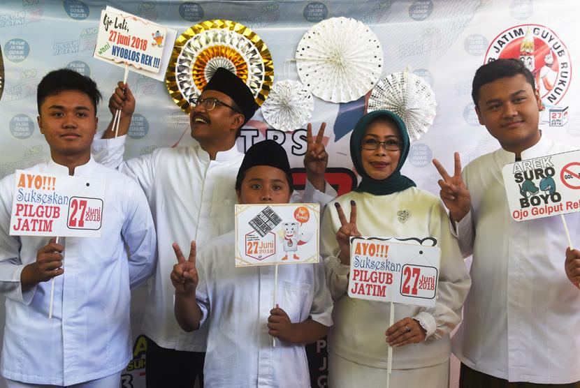 Calon Gubernur Jawa Timur Saifullah Yusuf (kedua kiri) bersama istri Fatma Saifullah Yusuf (kedua kanan) dan anak-anak berpose dengan atribut yang disediakan di tempat pemungutan suara (TPS) 3 di Gayungan, Surabaya, Jawa Timur, Rabu (27/6).