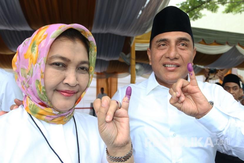 Calon Gubernur Sumatera Utara nomor urut satu Edy Rahmayadi (kanan) didampingi istri Nawal Lubis, menunjukkan jari kelingking usai memberikan hak suara pada Pilgub Sumut, di TPS 15, Lingkungan VII Pangkalan Masyhur, Medan Johor, Medan, Sumatera Utara, Rabu (27/6).