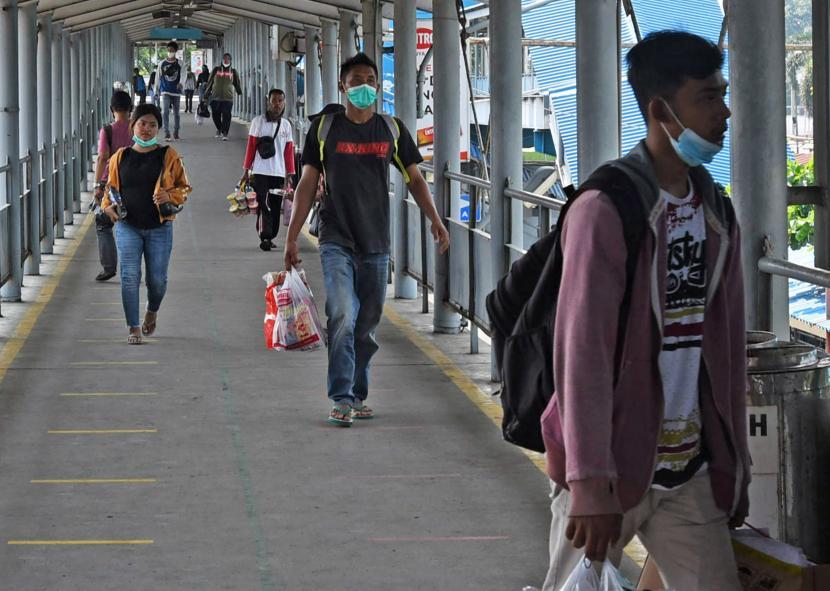 Calon penumpang kapal tujuan Sumatera melintas di Dermaga II Pelabuhan Merak, Banten, Ahad (18/4/2021). Adanya kebijakan pemerintah yang melarang mudik tanggal 6-17 Mei mendatang untuk mencegah penyebaran COVID-19 mendorong sebagian warga mudik lebih awal.