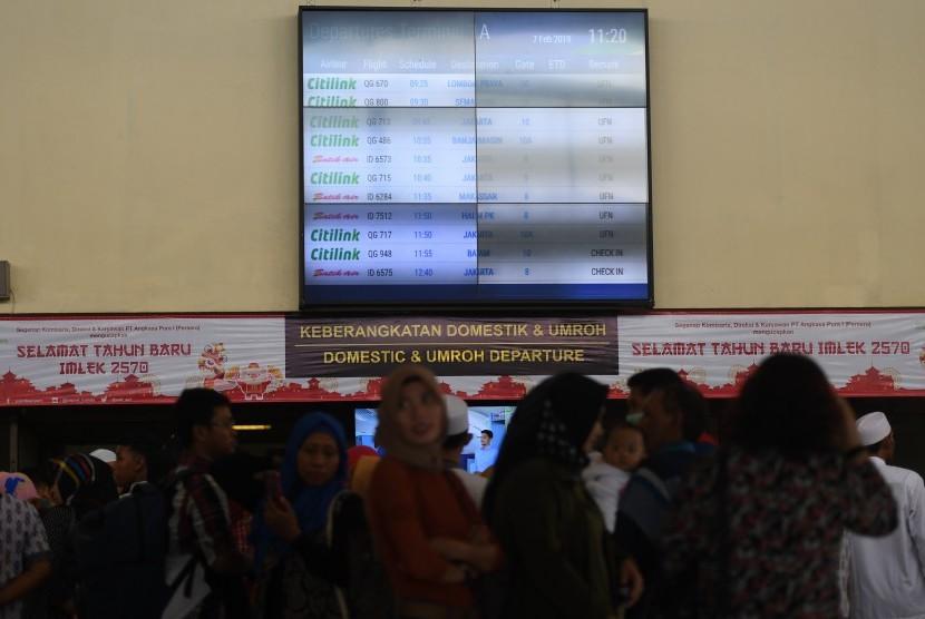 Calon penumpang mengamati layar informasi penerbangan di terminal keberangkatan domestik 1A Bandara Internasional Juanda Surabaya, Sidoarjo, Jawa Timur, Kamis (7/2/2019).
