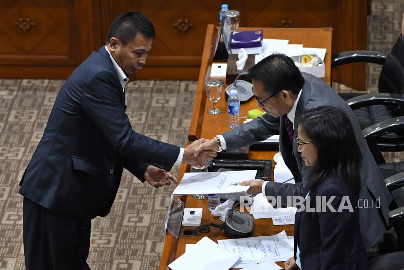 Calon pimpinan KPK Nawawi Pomolango (kiri) menjabat tangan pimpinan sidang Komisi III DPR RI Herman Hery (tengah) usai menjalani uji kepatutan dan kelayakan di ruang rapat Komisi III DPR RI, Jakarta, Rabu (11/9/2019).
