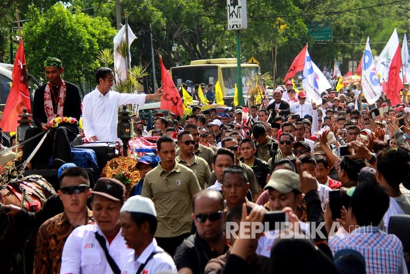 Calon Presiden nomor urut 01 Joko Widodo (kedua kiri) menyapa pendukungnya saat pawai kampanye terbuka di Ciceri, Serang, Banten Ahad (24/3/2019).