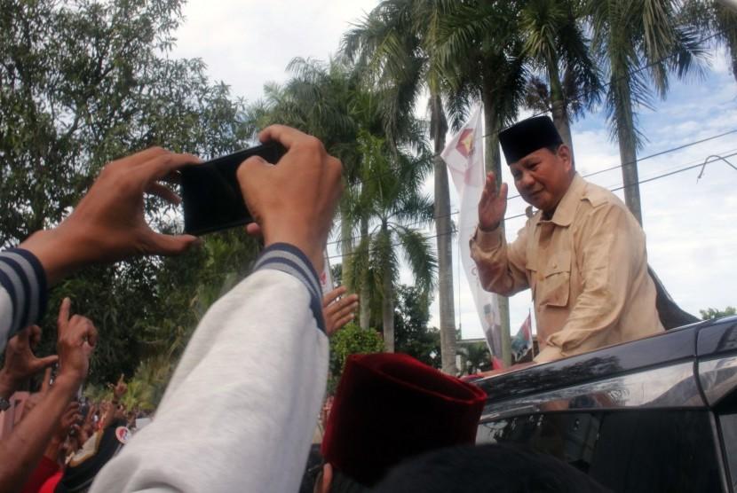 Calon Presiden nomor urut 02 Prabowo Subianto menyapa pendukungnya dari atas mobil saat berkampanye di Serang, Banten, Sabtu (16/3/2019).