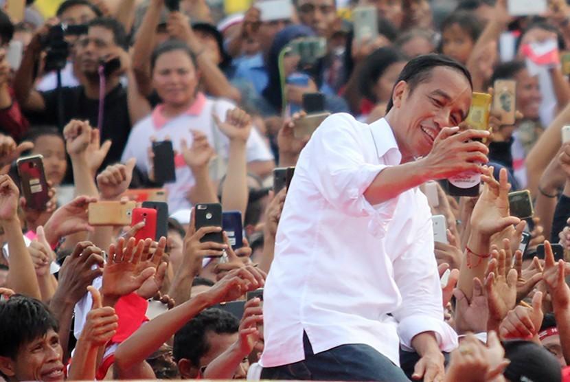 Calon Presiden petahana nomor urut 01 Joko Widodo berswafoto dengan massa pendukungnya saat melakukan kampanye terbuka di kota Dumai, Dumai, Riau, Selasa (26/3).