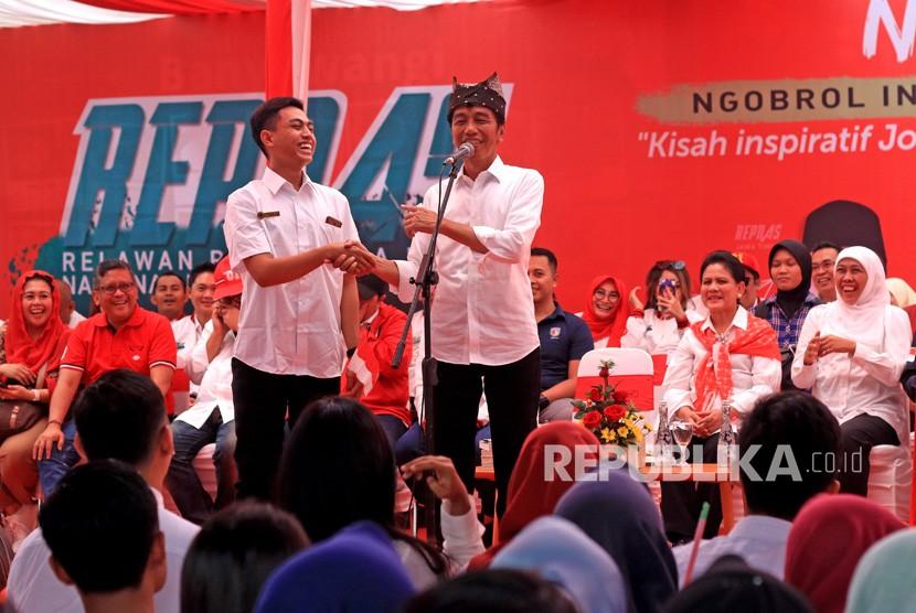 Calon Presiden petahana nomor urut 01 Joko Widodo (kanan) berbincang dengan salah satu relawan Pengusaha Muda Nasional (Repnas) saat menggelar kampanye Ngopi (ngobrol Inspirasi) di Banyuwangi, Jawa Timur, Senin (25/3/2019).