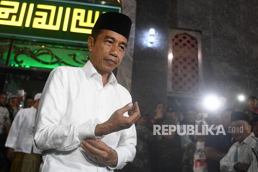 Calon Presiden petahana nomor urut 01 Joko Widodo mengancingkan lengan kemejanya usai menjalankan Salat Magrib berjamaah di Masjid Agung Brebes, Jawa Tengah, Kamis (4/4/2019).