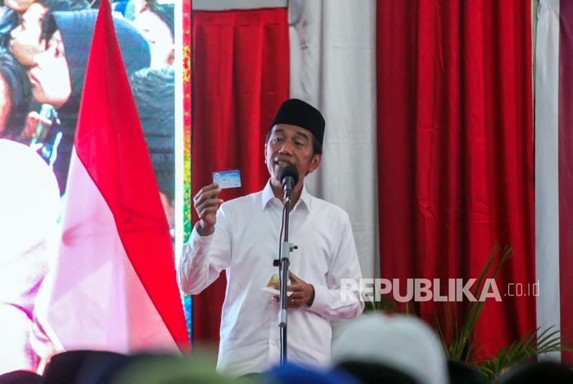 Calon Presiden petahana nomor urut 01 Joko Widodo menunjukkan kartu Pra Kerja saat berpidato dalam kampanye terbuka di Lhokseumawe, Aceh, Selasa (26/3/2019).