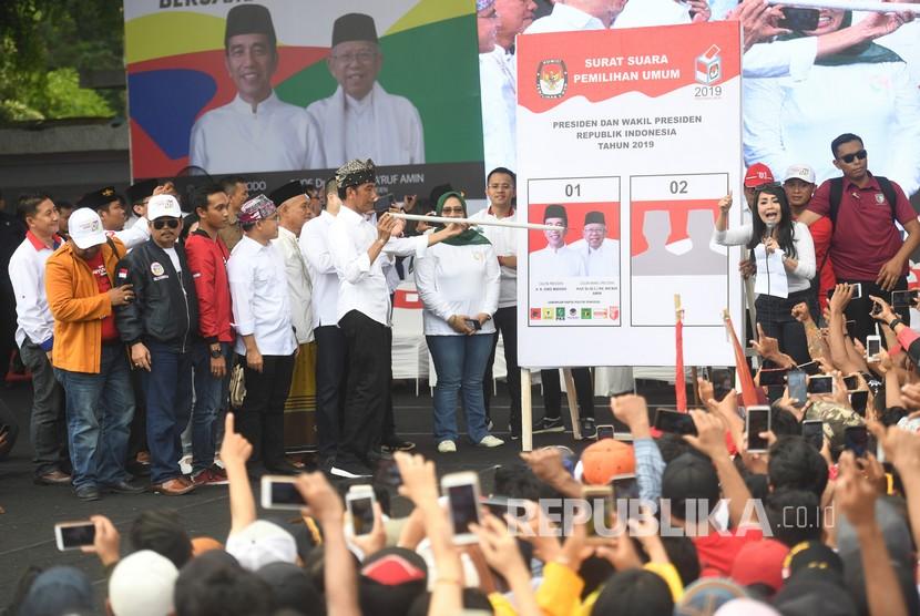 Calon Presiden pejawat nomor urut 01 Joko Widodo (tengah) memperagakan cara mencoblos saat kampanye terbuka di Banyuwangi, Jawa Timur, Senin (25/3).