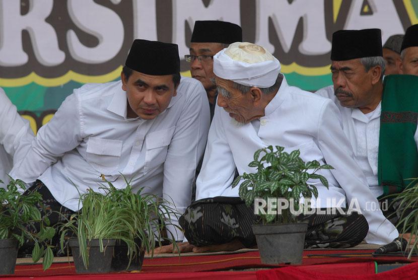 Calon wakil gubernur Jawa Tengah nomor urut 1 Taj Yasin (kiri) berdialog dengan ulama kharismatik yang juga ayahnya Maimoen Zubair (tengah) saat berlangsung Syawalan Akbar dan Doa Bersama di lapangan Soepadi Mungkid, Magelang, Jateng, Jumat (22/6).