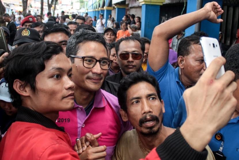 Calon Wakil Presiden nomor urut 02 Sandiaga Uno (tengah) menyapa pedagang ketika berkunjung ke Pasar Larangan, Sidoarjo, Jawa Timur, Selasa (1/1/2019).