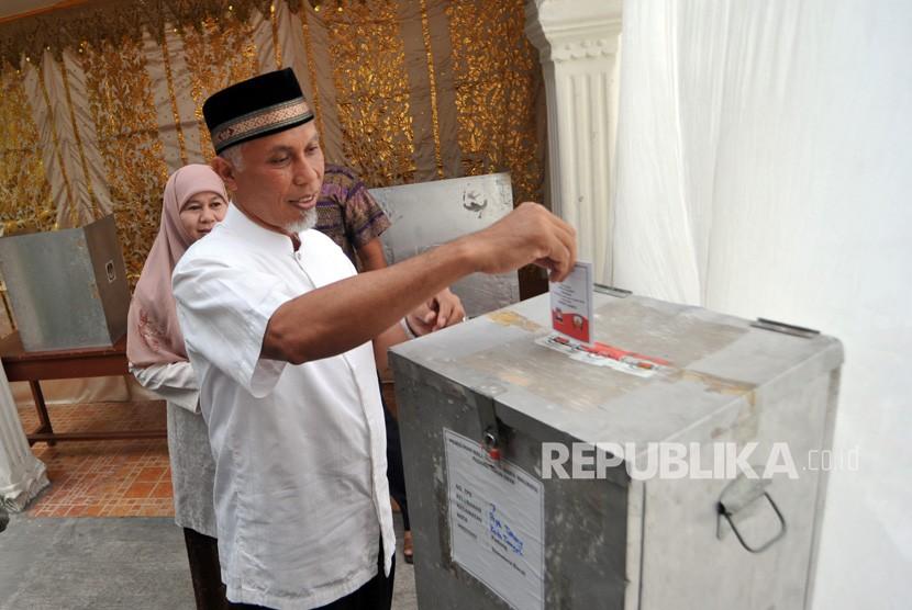 Calon Wali Kota Padang, Mahyeldi bersama istri, menggunakan hak pilih di TPS 7, Parupuk Tabing, Padang, Sumatera Barat, Rabu (27/6).
