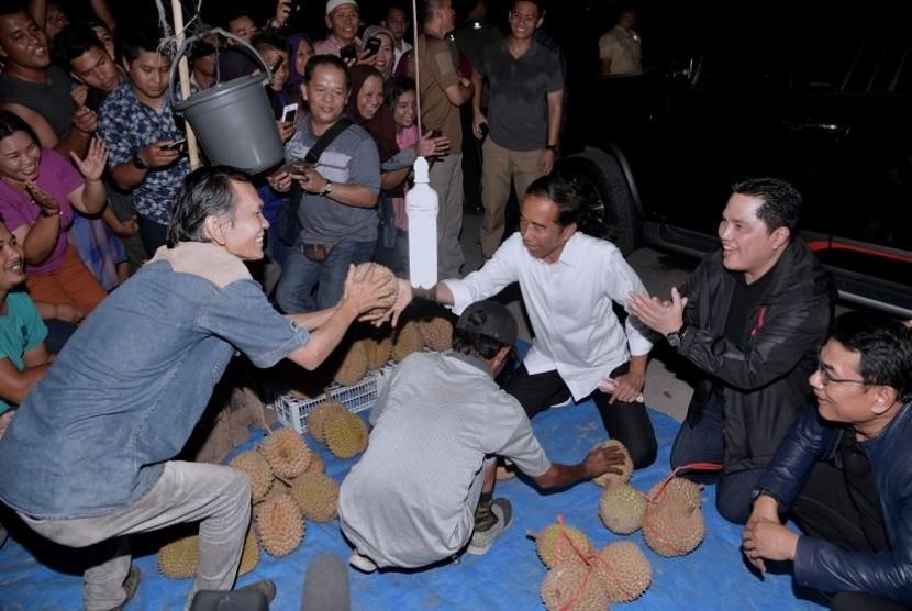 Capres 01 Joko Widodo (Jokowi) mencicipi durian yang dijajakan di pinggir jalan di Dumai usai menggelar kampanye..